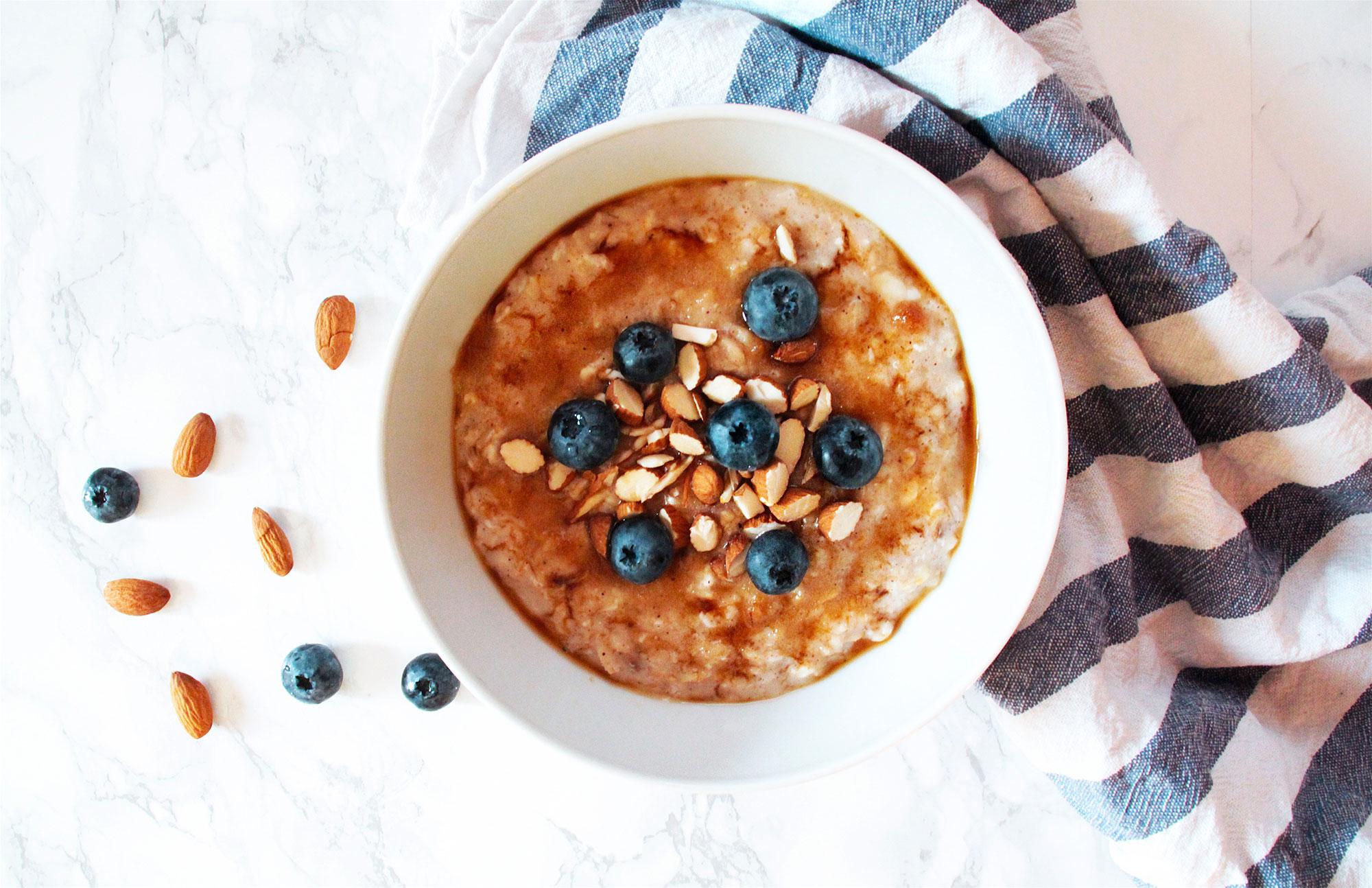 Kuva: Valkoisella tasolla lautasellinen kaurapuuroa, siniraitainen keittiöpyyhe, mustikoita ja manteleita.