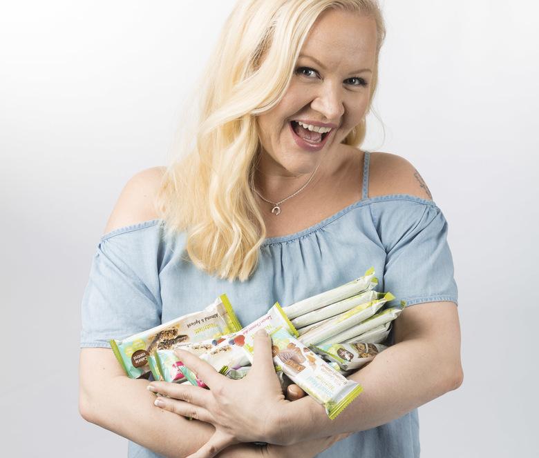 Henkilökuva: Nutrilett-lähettiläs Lotta Backlund pitää sylissään kasaa Nutrilett-patukoita.
