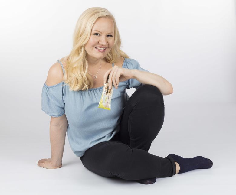 Henkilökuva: Siniseen paitaan ja mustiin housuihin pukeuttunut Lotta Backlund kädessään Nutrilett-välipalapatukka.
