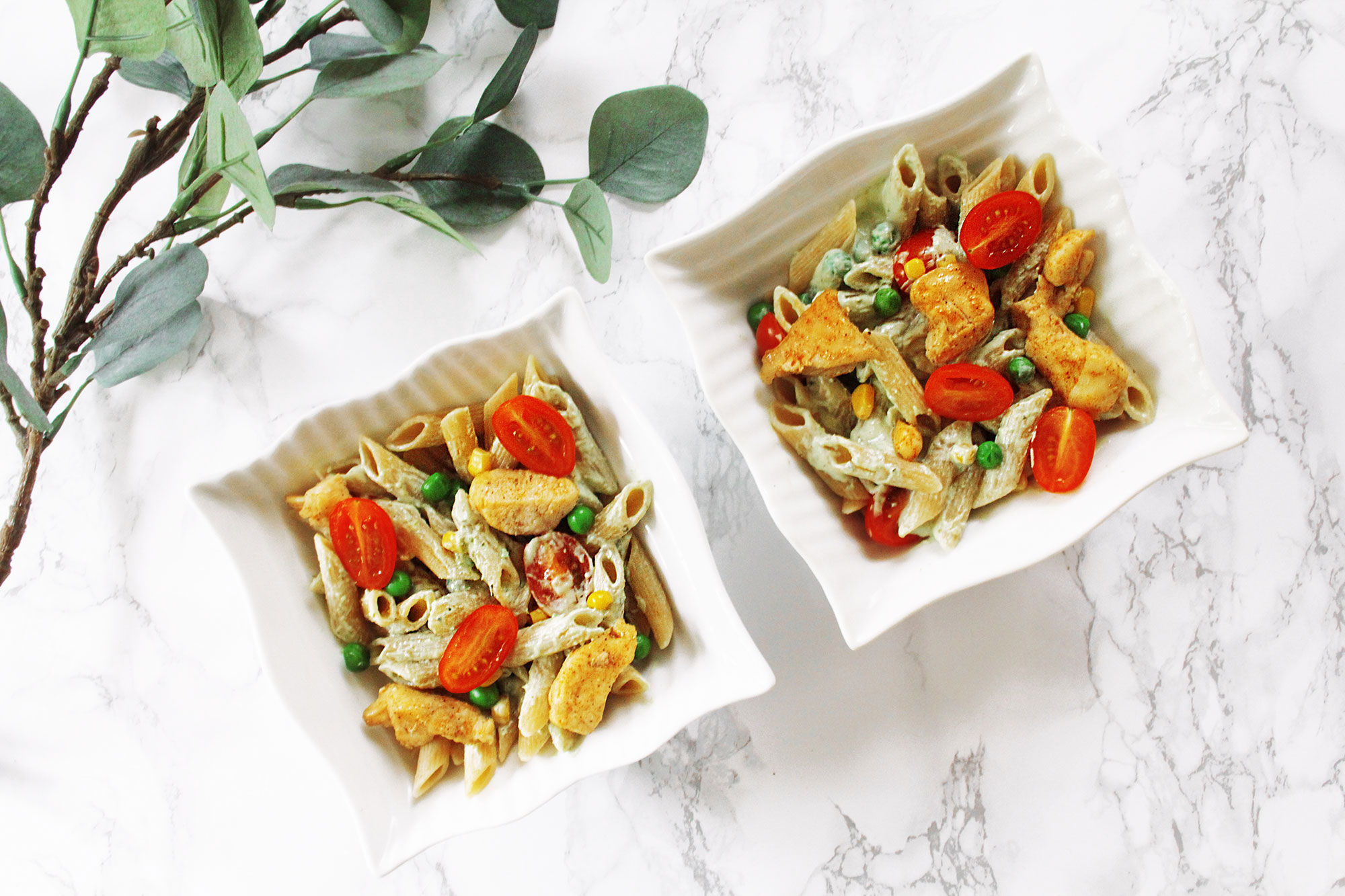 Tarjoiluehdotus: Kaksi neliönmuotoisissa lautasissa olevaa pasta-annosta, joissa koristeena kirsikkatomaatin puolikkaita.