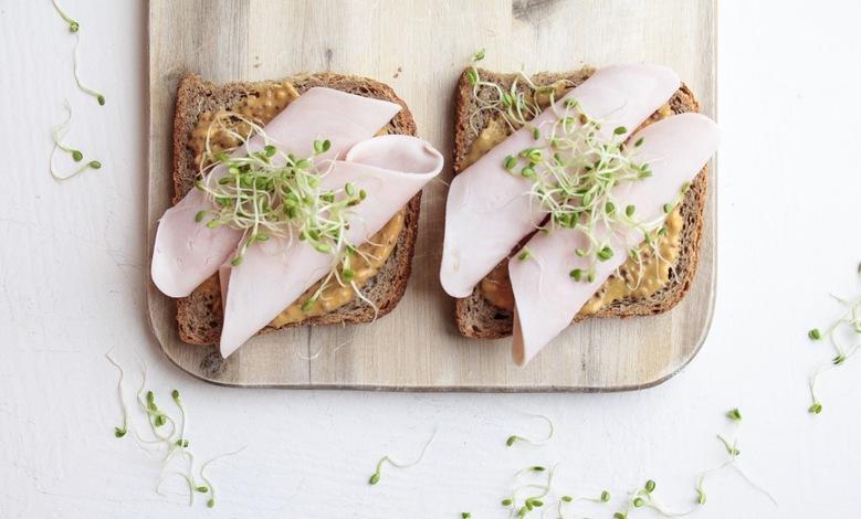 Terveellinen täysjyvävoileipä, jossa kalkkunaa, sinappia ja ituja