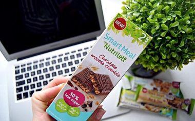 Kuva: Smart Meal by Nutrilett -tuotepakkaus. Taustalla kannettava tietokone, huonekasvi ja lisää 3 Nutrilett-patukaa.